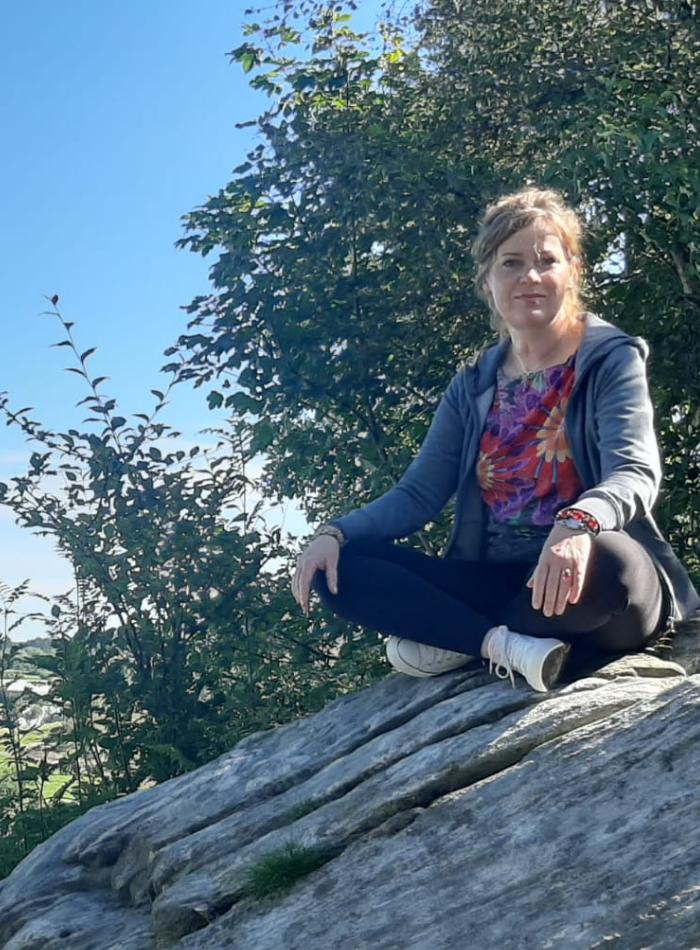 Joanna Klukojć siedząca na kamieniu na tle nieba